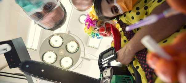 POV of a dentists and a clown holding a chain saw about to operate on a patient.