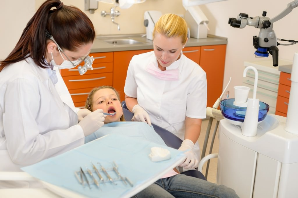 dental assistant with dentist and little child